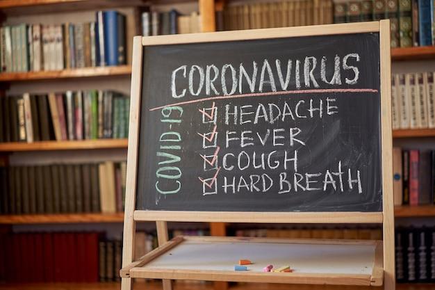 Коронавирус симптомы. головная боль. лихорадка. кашель. написано белым мелом на доске в связи с эпидемией коронавируса во всем мире. covid-19 пандемия