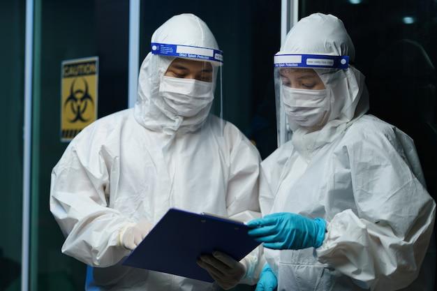 코로나 바이러스 테스트 프로세스 : 위험물 한 벌에 얼굴 방패가있는 의료 마스크를 착용하는 커플 과학자, 혈액 검사에 대한 정보가 포함 된 보고서.