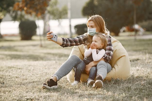 Тема коронавируса. семья в летнем парке. женщина в клетчатой рубашке.