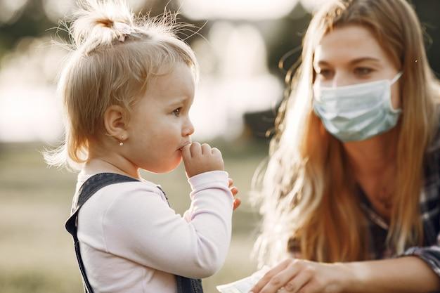 コロナウイルスのテーマ。サマーパークの家族。セルシャツの女性。
