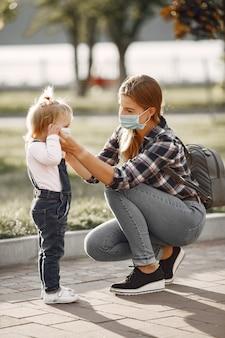 Tema coronavirus. famiglia in un parco estivo. donna in una camicia di cella. Foto Gratuite