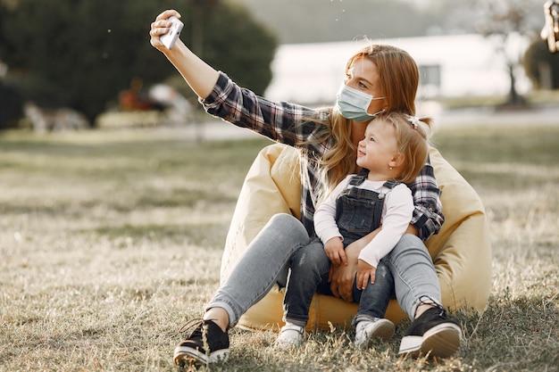 Tema coronavirus. famiglia in un parco estivo. donna in una camicia di cella.
