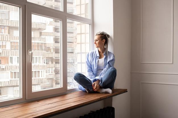 코로나 바이러스 테마. 집에있어. 창에 앉아 험 상을 꿈꾸는 소녀