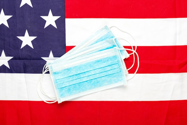 Coronavirus in usa. protective surgical face mask on american national flag.