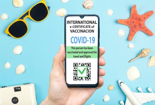 여행자 개념을 위한 코로나바이러스 백신 증명서 또는 백신 여권. 해외여행을 위한 스마트폰 모바일 앱의 코로나19 면역 전자여권. 선글라스와 파란색 배경,