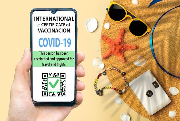 여행자 개념을 위한 코로나바이러스 백신 증명서 또는 백신 여권. 해외여행을 위한 스마트폰 모바일 앱의 코로나19 면역 전자여권. 모자와 함께 노란색 해변 배경