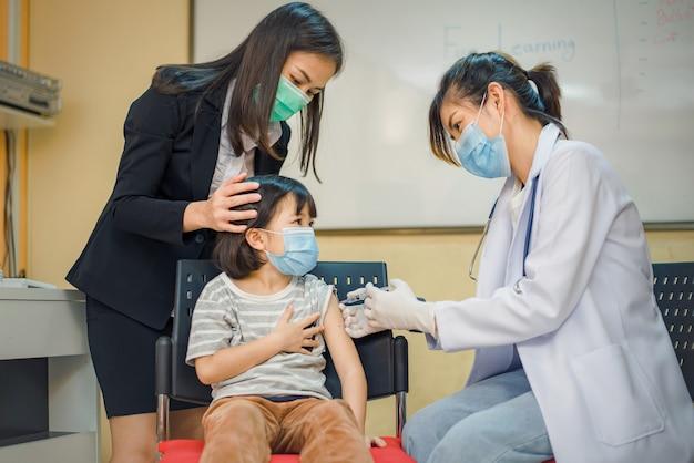 コロナウイルスワクチン接種。 covid19ワクチン。児童の深刻な流行を防ぐために、学校で学童に予防接種を行う医師。インフルエンザの予防接種を受けている少年。ウイルス予防。
