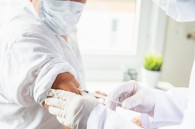 코로나 바이러스 예방 접종. 코로나 19 백신. 보호 마스크의 노인 환자를위한 covid-19 백신을 적용하는 수술 장갑 및 얼굴 마스크 의사.