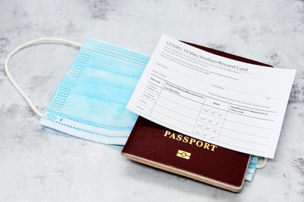 Карточка вакцинации против коронавируса, биометрический паспорт и синяя медицинская маска на светло-сером столе.