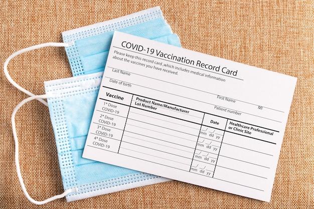 コロナウイルスワクチン接種記録カード。 2つの部分と注射器に分かれたサージカルマスク。 covid19を倒すコンセプト