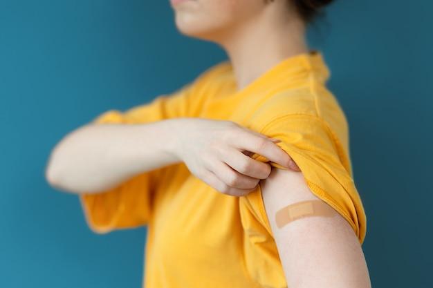 코로나바이러스 예방접종. 노란색 티셔츠를 입은 젊은 여성이 반창고가 붙은 손을 보여줍니다. 확대. 진한 파란색 배경입니다. 예방 접종 및 바이러스 보호의 개념입니다.