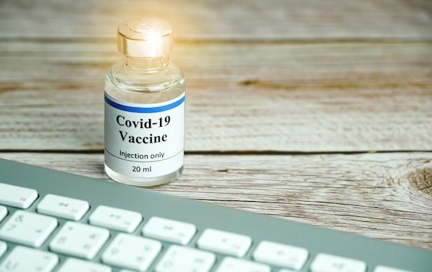 Coronavirus vaccine bottle with keyboard coronavirus vaccine online booking