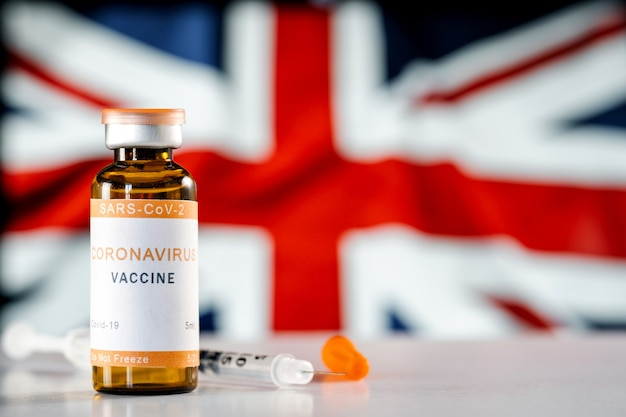 Coronavirus vaccine covid19 and a medical syringe on background of the flag of the united kingdom