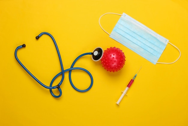 코로나 바이러스 백신, 진단. 바이러스 스트레인 및 주사기, 청진기, 노란색 마스크. 프리미엄 사진