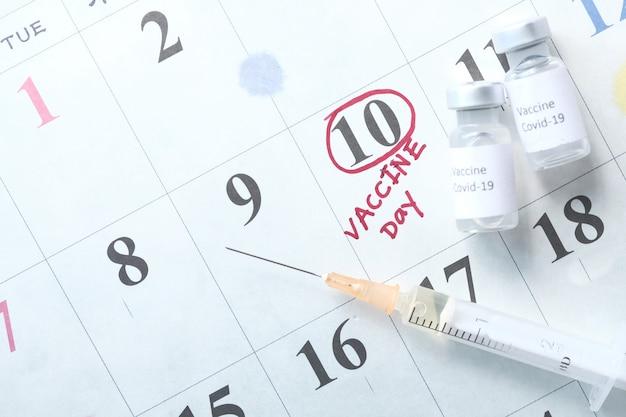 Coronavirus vaccine and syringe on calendar.