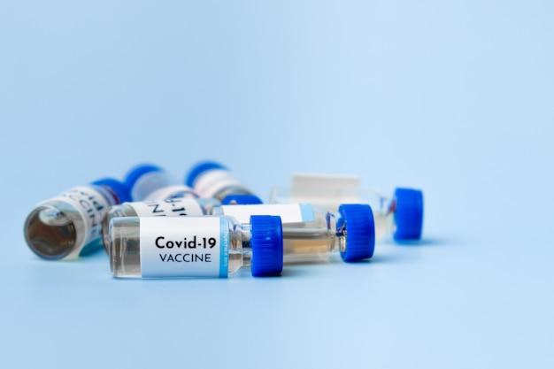 Флаконы вакцины против коронавируса на синем фоне с копией пространства.