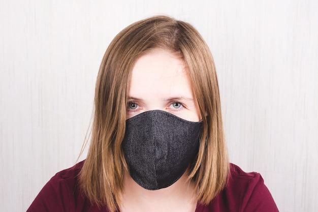 코로나 바이러스. 수제 보호 마스크를 착용 한 코로나 바이러스에 대한 격리 된 여성. 코로나 바이러스 전염병 동안 집에 머물러 있습니다.