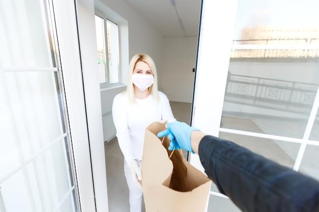 コロナウイルス。屋内で配達員から荷物を受け取る医療用マスクとゴム手袋を着用している女性。ウイルスの予防とプロトコル。家にいる。配達サービス。パッケージの消毒。