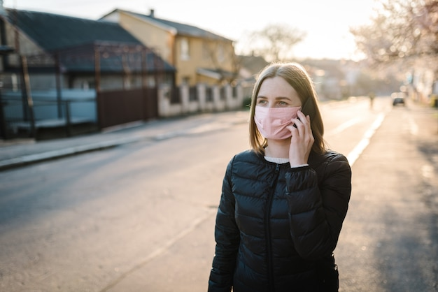 コロナウイルス。携帯電話で話している通りを歩いて医療用防護マスクを着ている女性
