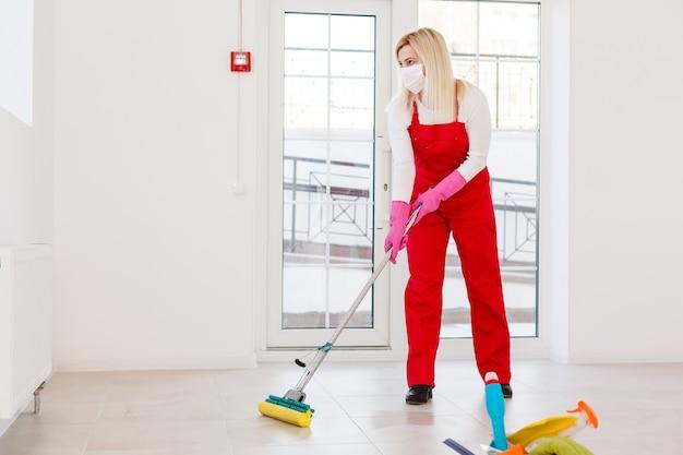 コロナウイルス。フェイスマスクの女性がコロナウイルスの流行中に家を掃除して消毒しました。 covid-19感染の防止。コロナウイルスの拡散を止めます。