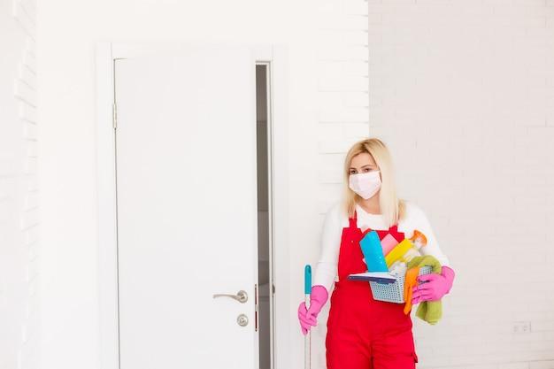 コロナウイルス。コロナウイルスの流行中に彼女の家を掃除し、消毒するフェイスマスクを持つ女性。 covid-19感染の予防。コロナウイルスの拡散を阻止します。