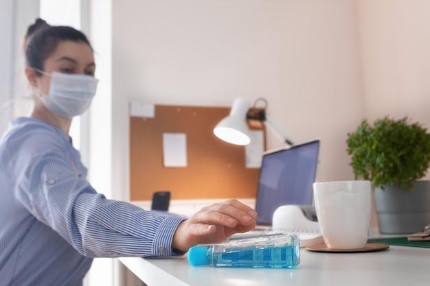 Коронавирус. женщина работает из дома в защитной маске в карантине. концепция домашнего офиса во время covid-19