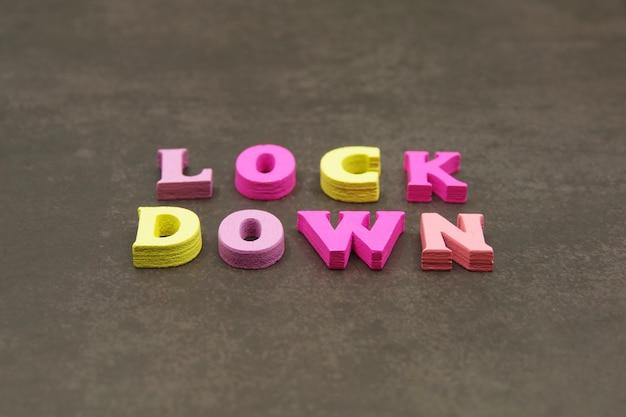コロナウイルスの世界封鎖wordlockdownは、茶色の表面に木製の文字で配置されています旅行の社会的相互作用に厳しい制限を課します医療およびcovid19パンデミックの概念