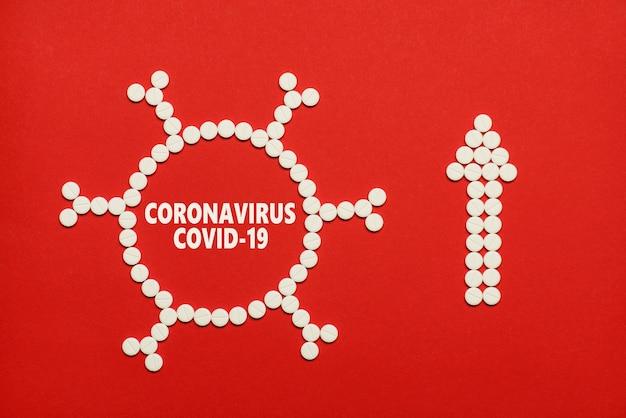 コロナウイルスの世界を広める概念。ウイルスと矢印の形をしたタブレットのフラットレイオーバーヘッドクローズアップビュー写真の上の上部は、コピー空白の空のスペースで孤立した赤い色の背景を示しています