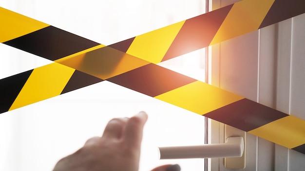 Желтая лента коронавируса оставайся дома. рука тянется к дверной ручке, чтобы открыть дверь и выйти. опасность заражения. карантин