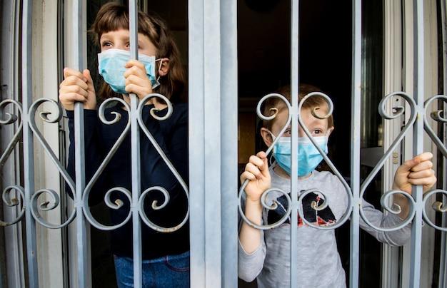 コロナウイルス家庭で隔離された幼児は、窓から外を見て病気のウイルスが広がるのを防ぐフェイスマスク保護具を着用して自動検疫