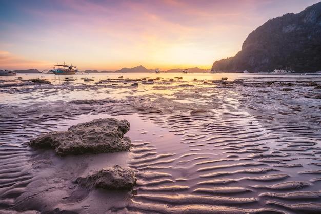 코롱 비치, 엘니도, 필리핀. 열 대 해변에서 일몰입니다. 황금 시간에 태양 반사
