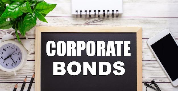 Корпоративные облигации, написанные рядом с карандашами, смартфоном, белым блокнотом и зеленым растением в горшке