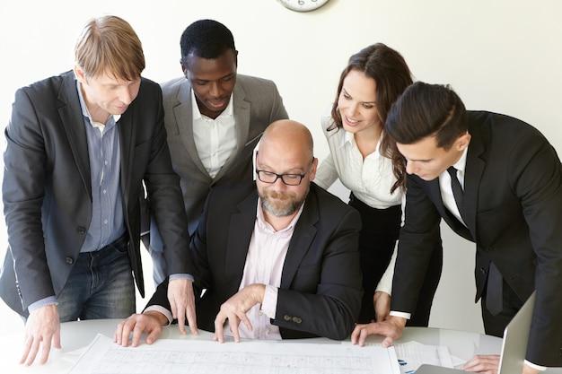 Корпоративный мозговой штурм и работа над крупным проектом в дизайн-бюро. четверо коллег в офисной одежде стоят и внимательно следят за схемами. рисунки лежат на столе возле своего главного лидера.
