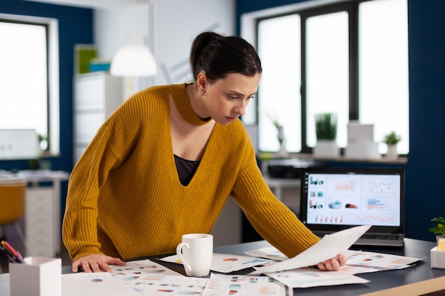 Corporate business woman reading statistics on documents paperwork executive entrepreneur, manager leader standing working on deadline documents projects.