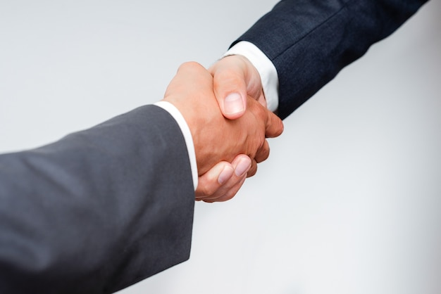 Рукопожатие корпоративных бизнесменов в помещении. два человека, профессионально одетые, жестикулируют вместе. рабочие коллеги-партнеры подписывают соглашение о заключении контракта