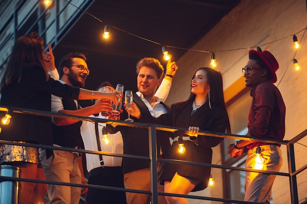 夏の夜の若い友人のランプの暖かい光の中で祝う企業