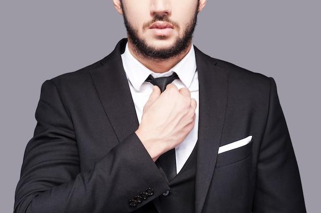 企業の自信は並外れたスタイルを満たしています。灰色の背景に立っている間彼のネクタイを調整するファッショナブルな若い男のトリミングされた画像