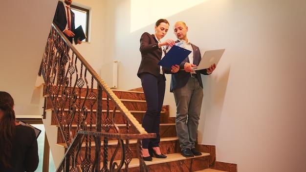 ビジネスビルの階段で実業家と話しているラップトップを保持している企業のエグゼクティブマネージャー。現代のオフィスで残業しているチームのプロの成功した起業家
