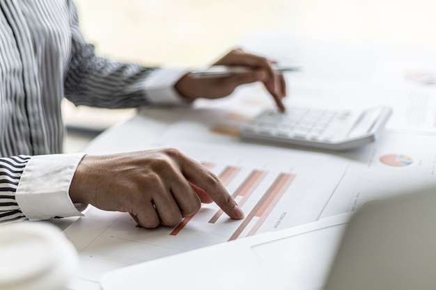 A corporate financier is checking financial documents for the correctness of the financial statements, she is checking the numbers on the documents using a calculator to calculate. finance concept.