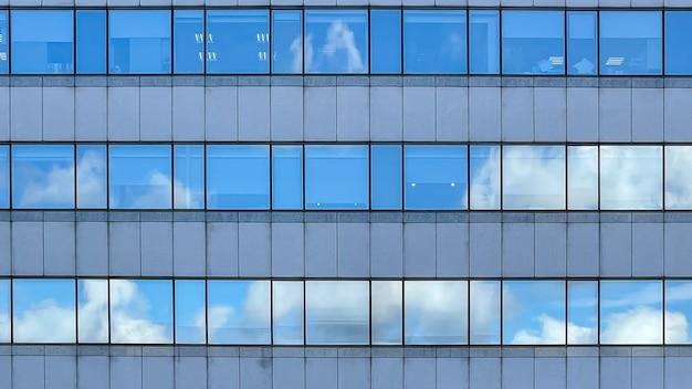 Горизонт корпоративной достопримечательности в современном городе. высокие стеклянные небоскребы, отражающие деловые здания вокруг них. голубое небо и высокие здания в столице.