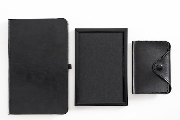 Корпоративный образ жизни. набор принадлежностей офисного работника. плоская планировка визитницы, пустая фоторамка, адресная книга