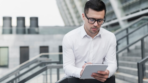 Corporate man writing in notepad