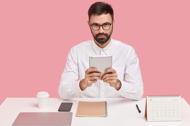 Corporate manager uses touchpad for accounting, wears optical glasses and white shirt, checks report, analyzes budget