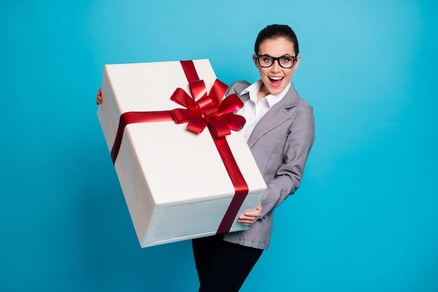 Концепция корпоративной вечеринки празднует юбилей. шокированная позитивная девушка, агент-брокер, получает подарочную коробку с пакетом большой огромной мечты, одетая в серый пиджак, изолированный синий цвет фона
