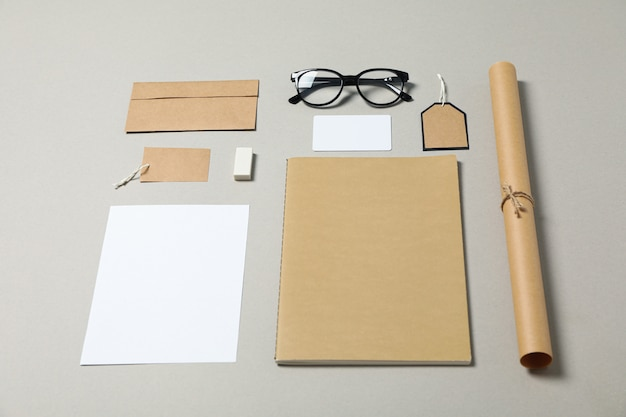 企業の文房具と灰色の背景上の眼鏡
