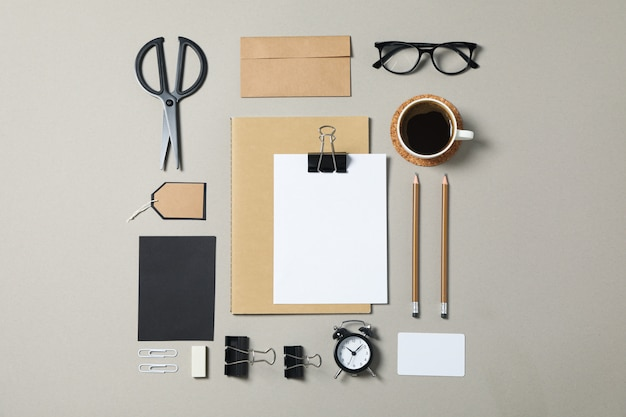Corporate stationery, glasses and alarm clock on grey background.