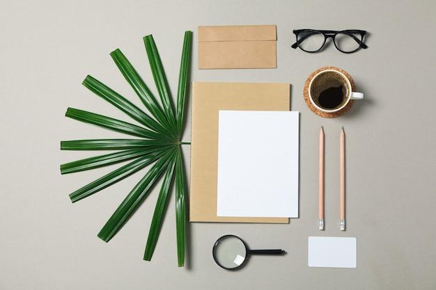 灰色の背景に企業の文房具、メガネ、シュロを葉します。
