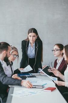 기업 팀워크. 비즈니스 전략 개발. 마케팅 아이디어를 듣고 여자 teamlead. 회색 배경에 공간을 복사합니다.