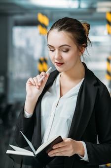 회사 여자 직원 초상화입니다. 사업은 계획을 중요시합니다. 사무실 작업 공간에서 하루 플래너와 인턴 미소.