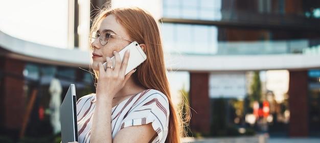 화창한 날 동안 전화와 노트북으로 포즈를 취하는 안경과 주근깨가있는 기업 여성